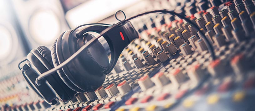 Pair of headphones sit on a mixing baord in a radio broadcast studio