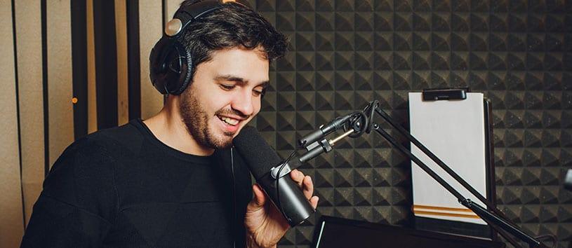 Man speaks into microphone in sound-proofed radio studio.