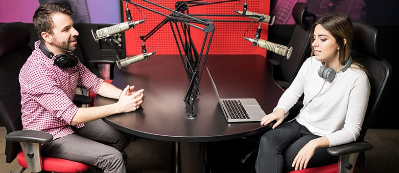 Man and woman speaking to each other through microphones at a radio broadcast studio