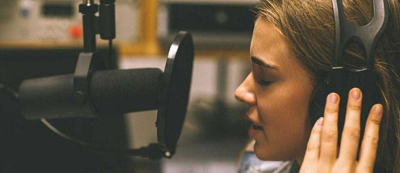 Young woman speaks into microphone at a radio broadcasting studio